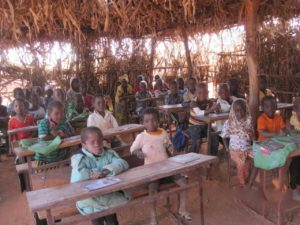 Children learning in a temporary classroom.